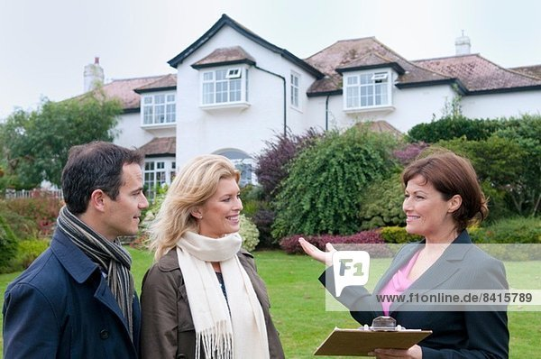 Mittleres erwachsenes Paar und Immobilienmaklerin außerhalb des Hauses