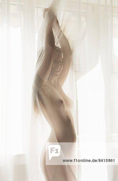 Nackte Frau hinter dem Vorhang