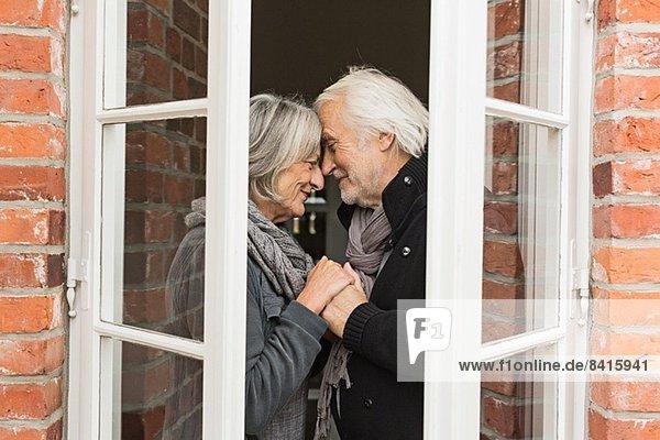 Seniorenpaar von Angesicht zu Angesicht durchs Fenster