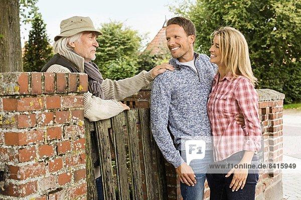 Älterer Mann  der sich auf das Tor stützt und mit einem mittleren erwachsenen Paar redet.