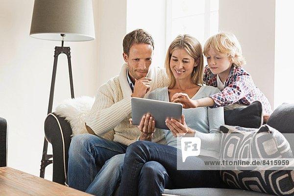 Eltern und Sohn mit digitalem Tablett