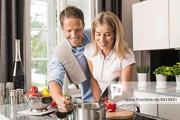 Mittleres erwachsenes Paar  das Essen zubereitet
