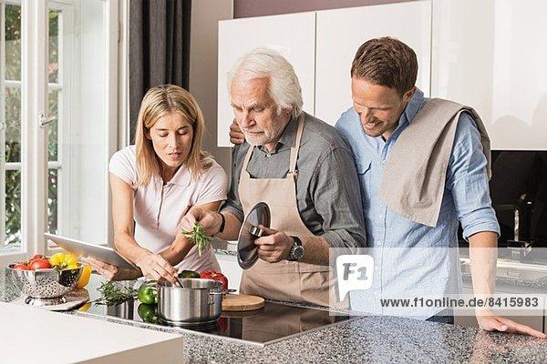 Älterer Mann mit mittlerem erwachsenem Paar bei der Zubereitung des Essens