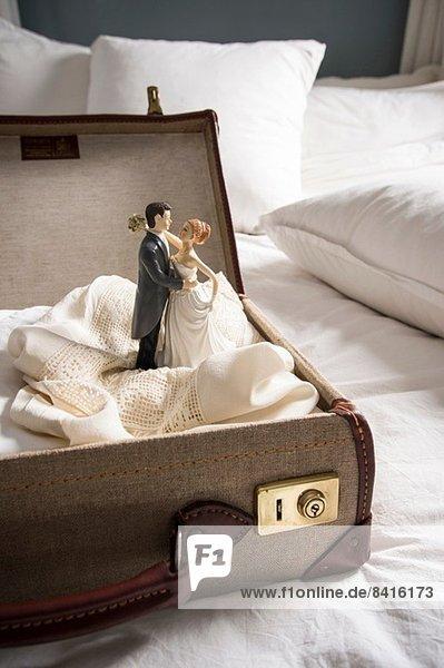 Offener Koffer auf Bett mit Hochzeitsfiguren