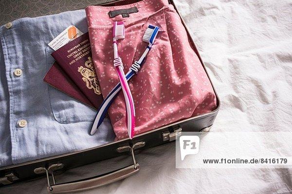 Offener Koffer auf dem Bett mit britischen Pässen und rosa und blauen Zahnbürsten