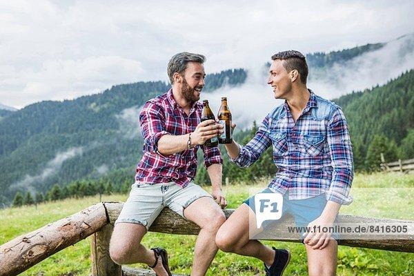 Zwei männliche Freunde trinken Bier am Zaun  Tirol Österreich