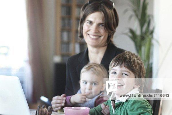 Mutter beim Frühstück mit Kindern vor der Arbeit