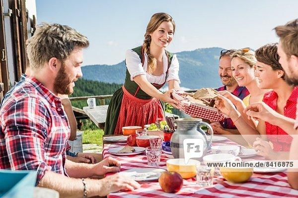 Freundeskreis beim Frühstück außerhalb des Chalets  Tirol  Österreich Freundeskreis beim Frühstück außerhalb des Chalets, Tirol, Österreich