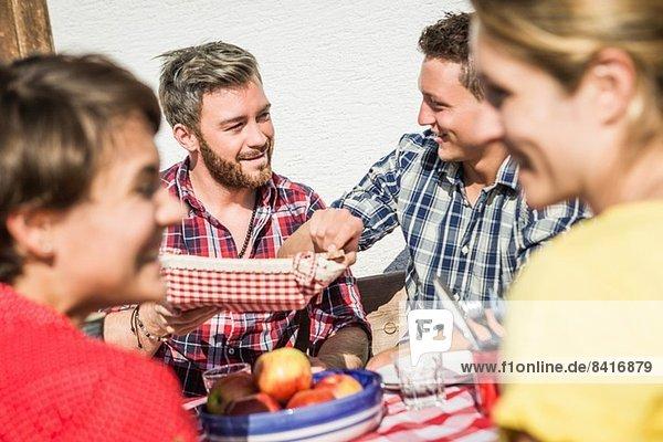 Freundeskreis beim gemeinsamen Frühstück im Freien