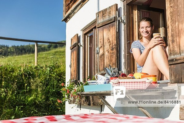 Frau schaut aus dem Chaletfenster  Tirol  Österreich