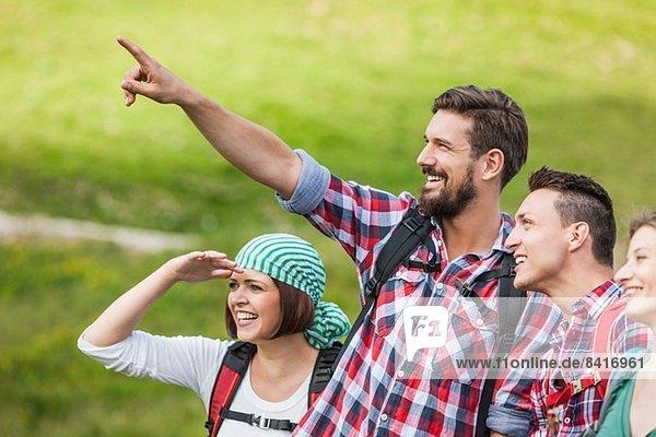 Freunde auf einer Wanderung  junger Mann zeigt auf