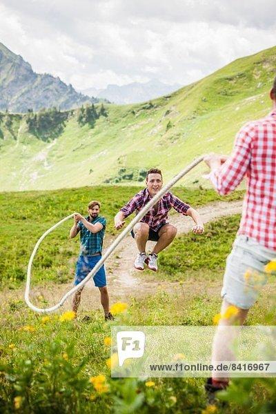Junger Mann springt mit Seil  Tirol  Österreich