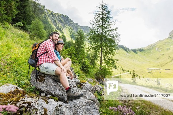 Young couple sitting on rocks  Tyrol  Austria