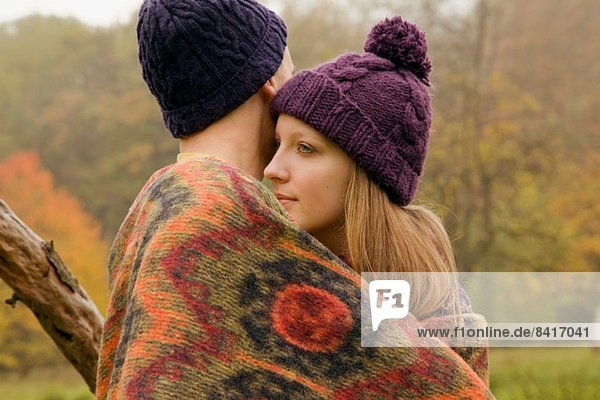 Close up of young couple wrapped in blanket in misty park