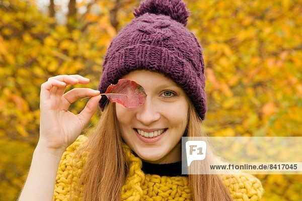 Close up of young woman in park holding autumn leaf over her eye