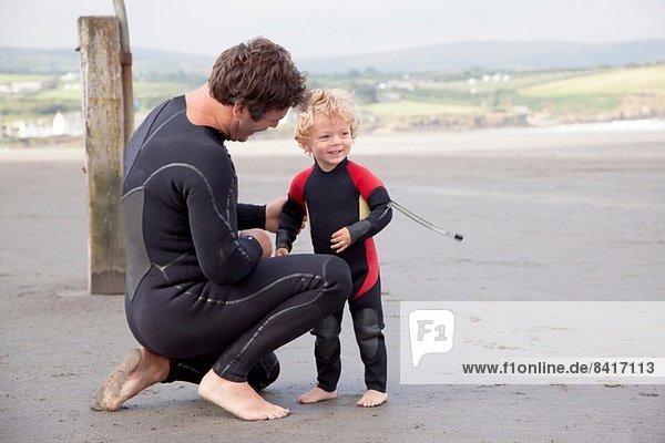 Vater und Sohn am Strand in Neoprenanzügen