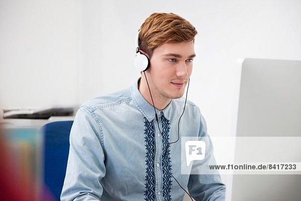 Junger Mann mit Kopfhörer im Büro
