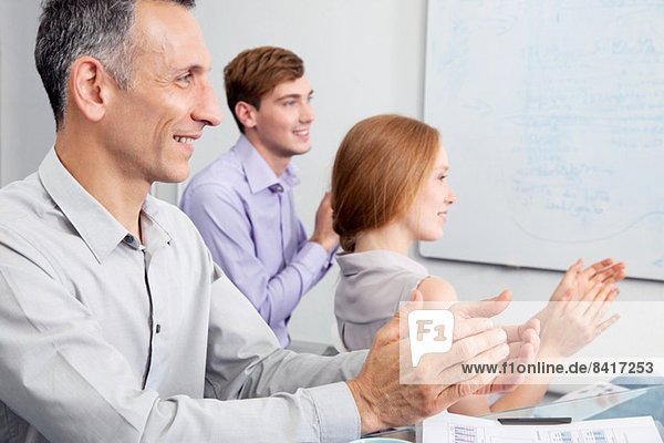 Business colleagues clapping in meeting