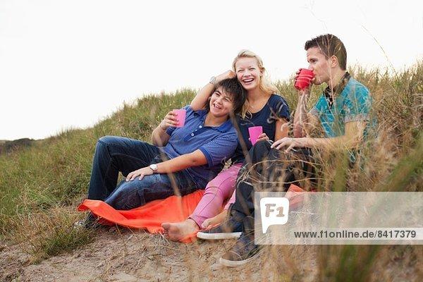 Jugendliche sitzen auf Müllbeutel  trinken