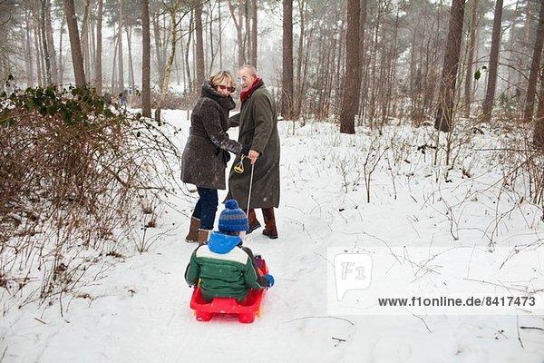 Großeltern ziehen Enkel auf Schlitten im Schnee