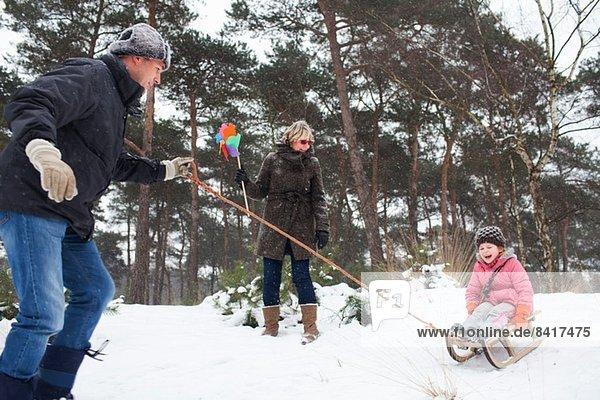 Vater und Großmutter ziehen Mädchen auf Schlitten im Schnee