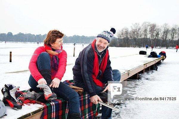 Paar auf dem Pier sitzend  auf Schlittschuhen sitzend