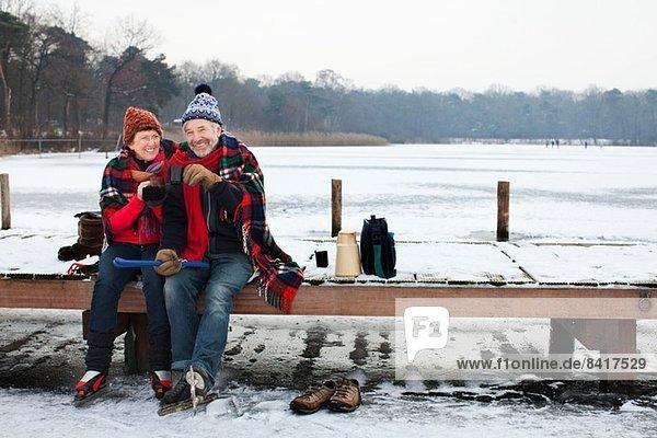 Ein Paar sitzt auf dem Pier und trinkt etwas Heißes