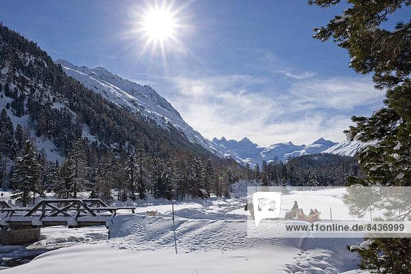 Frau Berg Winter Mann Schlitten Kanton Graubünden