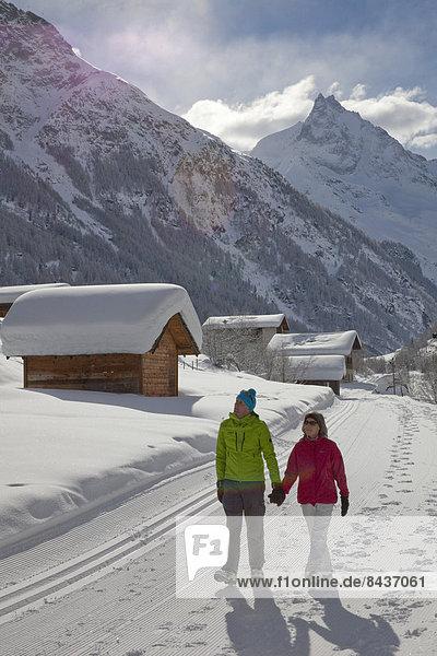 Frau Winter Mann gehen folgen Weg Dorf wandern 2 Wanderweg Schnee Wintersport