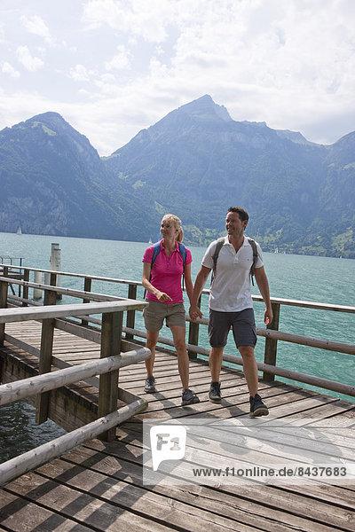 Fußgängerbrücke Frau Mann gehen folgen Weg wandern Wanderweg Vierwaldstättersee Zentralschweiz