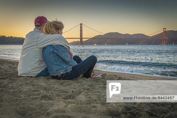 USA  Kalifornien  San Francisco  reifes Paar am Strand an der Golden Gate Bridge bei Dämmerung