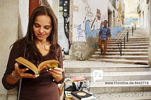 Portugal  Lisboa  Baixa  Rua do Madalena  junge Frau mit Buch stehend vor dem Antiquariat