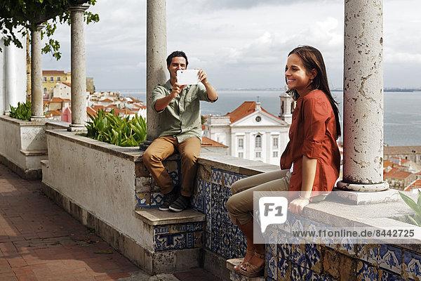Portugal  Lisboa  Alfama  Miradouro de Santa Luzia  junger Mann beim Fotografieren mit Mini-Tablette
