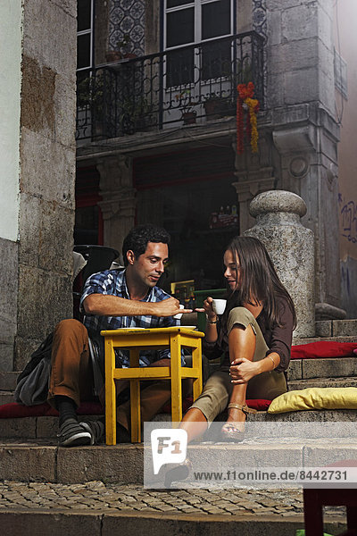 Portugal  Lisboa  Bairro Alto  young couple sitting at street cafe at dusk