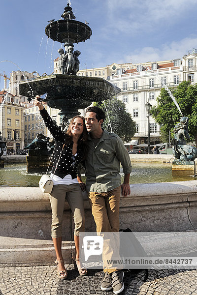 Portugal  Lisboa  Baixa  Rossio  Praca Dom Pedro IV  junges Paar fotografiert sich vor einem Springbrunnen