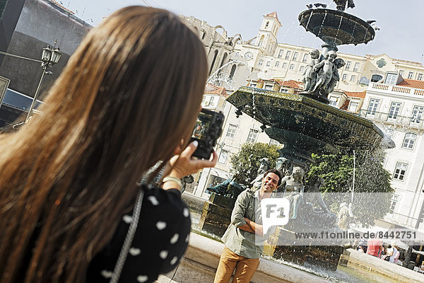 Portugal  Lisboa  Baixa  Rossio  Praca Dom Pedro IV  young couple photographing in front of a fountain