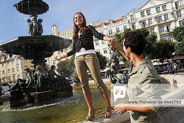Portugal  Lisboa  Baixa  Rossio  Praca Dom Pedro IV  junge Frau  die auf dem Rand eines Brunnens balanciert.