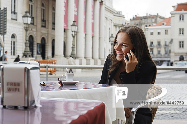 Portugal  Lisboa  Baixa  Rossio  Praca Dom Pedro IV  Teatro Nacional  junge Frau beim Telefonieren im Straßencafé