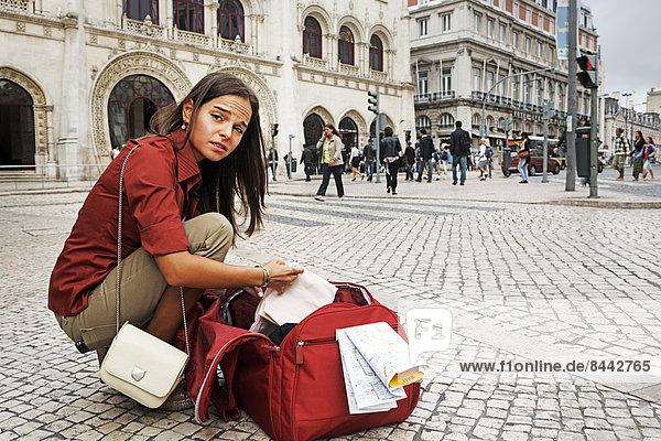 Portugal  Lisboa  Baixa  Rossio  verzweifelte junge Frau mit Stadtplan und Reisetasche