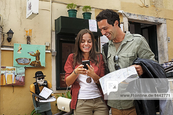 Portugal  Lisboa  Carmo  Calcada du Duque  young couple with city map and smart phone trying to orientate
