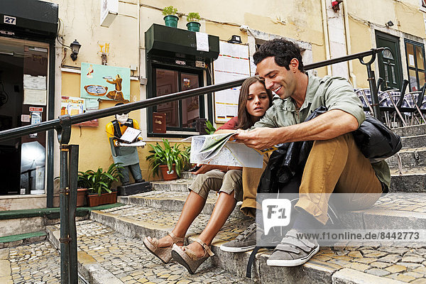 Portugal  Lisboa  Carmo  Calcada du Duque  young couple with city map sitting at stairs