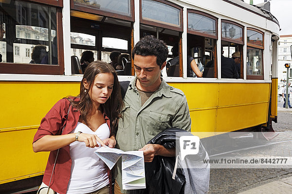 Portugal  Lisboa  Baixa  Rossio  young couple with city map in front of tram