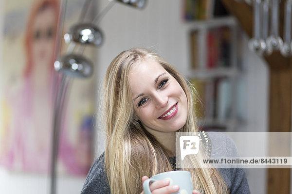 Porträt einer lächelnden jungen Frau mit Teetasse