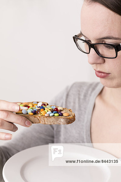 Junge Frau hält Brot  garniert mit vielen Tabletten