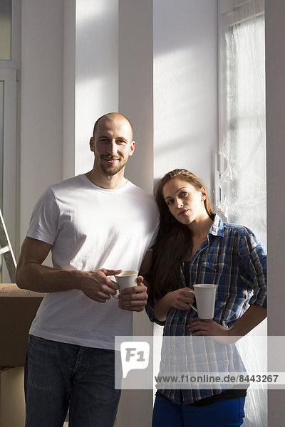 Young couple moving into new home  taking a coffee break