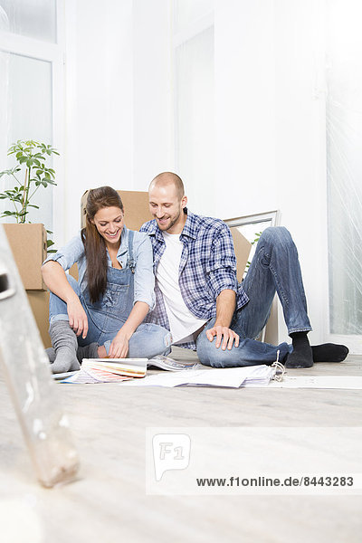 Young couple moving into new home  looking at color sample