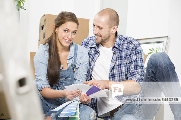 Young couple moving into new home  discussing color sample