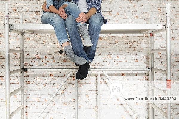Junges Paar zieht in ein neues Zuhause ein  sitzt auf einem Gestell und umarmt sich.