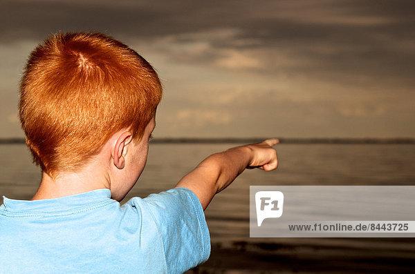 Flensburger Förde  Junge zeigt auf See