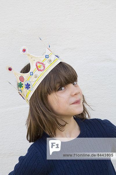 Porträt des kleinen Mädchens mit Papierkrone auf dem Kopf Porträt des kleinen Mädchens mit Papierkrone auf dem Kopf